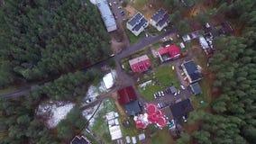 Vertikaler Flug über Fernsehturmhäusern und -wald stock footage