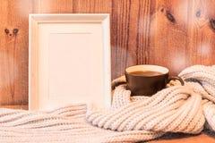 Vertikaler leerer weißer Holzrahmen und Becher mit Kaffee Lizenzfreie Stockbilder