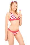 Vertikaler Schuss einer Frau im Bikini eine Eiscreme essend Stockbild