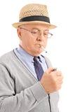 Vertikaler Schuss eines älteren Beleuchtens herauf eine Zigarette Stockfotografie