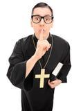 Vertikaler Schuss eines männlichen Priesters, der Finger auf Lippen hält Lizenzfreies Stockfoto