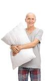 Vertikaler Schuss eines Seniors, der ein Kissen umarmt Lizenzfreie Stockbilder