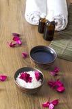 Vertikaler Schuss Vorbereitung für Massagetherapie Schüsseln mit kosmetischen Waren und der Blumenblattherstellung entspannen sic lizenzfreie stockfotografie