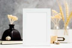 Vertikaler weißer Fotorahmenspott oben mit trockenen Anlagen im Vase, im Notizbuch und in den Holzhäusern auf Regal Skandinavisch Stockbild