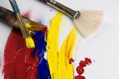 Vertikales Bild des weißen Segeltuches und der Acrylfarbe und der Bürsten stockfotografie
