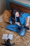 Vertikales Bild einer jungen Frau auf dem Bett im Schlafzimmer stimmt seine Gitarre ab und schreibt ein Blog auf eine DSLR-Kamera Lizenzfreie Stockbilder