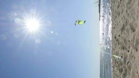 Vertikales Clip mit kitesurfers mit hochfliegenden Drachen gegen blauen Himmel stock video