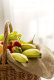 Vertikales Detail eines Korbes voll der Früchte auf einem hellen Hintergrund - hoher Schlüssel Stockfoto