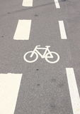 Vertikales Fahrradzeichen auf Asphalt mit weißen Streifen Stockfotos