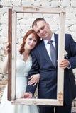 Vertikales Foto der Braut und des Bräutigams, die durch Porträtrahmen schauen Stockfotografie