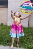 Vertikales frontales Foto des kleinen Mädchens im Regenbogen farbigen Sommerkleid, das mehrfarbigen Wasserball wirft lizenzfreie stockfotografie