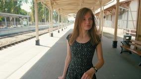 Vertikales Panorama der Frau gehend auf Station mit Koffer, Wartezug stock video