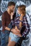 Vertikales Porträt eines liebevollen Paares auf Graffitihintergrund Stockbild