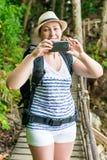 vertikales Porträt eines Touristen mit einem Telefon und einem Rucksack Stockbilder