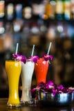 Vertikales Stillleben mit 3 Cocktails und Orchidee blüht im b Stockbild