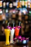 Vertikales Stillleben mit 3 Cocktails und Orchidee blüht im b Stockfoto