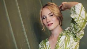 Vertikales Video Porträt der schönen schwangeren Frau im grünen Kleid, das die Kamera untersucht und aufwirft Langsame Bewegung stock video