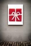 Vertikales weißes Brett und rote Geschenkbox, auf Grungy Gray Wall Stockfotografie