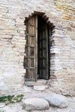 Vertikalt foto av en träöppen dörr i en forntida fästningvägg i Izborsk arkivfoto