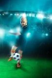 Vertikalt foto av fotbollspelaren som skjuter en boll i leken Arkivbilder