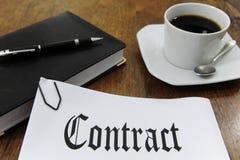 Vertrag und Kaffee auf einem Schreibtisch stockbilder