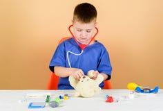 Vertragingen en wapens Het jonge geitje weinig bezige arts zit lijst met medische hulpmiddelen Algemeen medisch onderzoek Het con stock foto