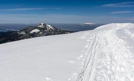 Vertrappelde weg in de sneeuw door wandelaars en sporen van skiërs op de rand in de bergen Royalty-vrije Stock Afbeeldingen