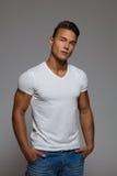 Vertrauens-gutaussehender Mann im weißen T-Shirt Stockfotos