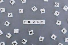 Vertrauenswort gemacht vom quadratischen Buchstabewort auf grauem Hintergrund lizenzfreie stockfotos