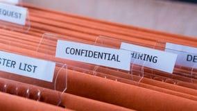 Vertrauliche Belegdatei halten im Ordnerkabinett lizenzfreie stockbilder