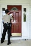 Vertreibungsmitteilung, die zur Tür von einem Gesetzeshüter aufgenommen wird Lizenzfreie Stockfotos