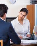 Vertreter, das auf Kunden hört und in der Agentur lächelt Lizenzfreie Stockbilder