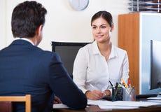 Vertreter, das auf Kunden hört und in der Agentur lächelt Lizenzfreies Stockfoto