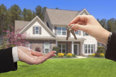 Vertreter Handing Over die Haus-Schlüssel vor neuem Haus Lizenzfreie Stockfotografie