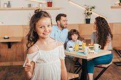 Vertretungsdaumen des kleinen Mädchens oben im Café mit ihrer glücklichen Familie verwischte lizenzfreies stockfoto