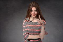 Vertretungsmisstrauen des jungen Mädchens gegen den dunklen Hintergrund Lizenzfreie Stockfotos