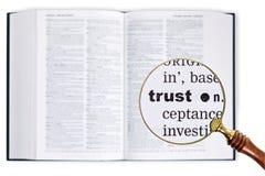 Vertrouwen door een vergrootglas over Woordenboek. stock foto