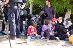 Övervaka att bevaka den väntande linjen av flyktingar i Tovarnik Arkivfoton