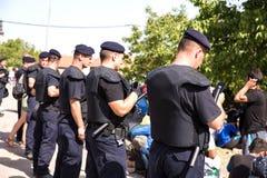 Övervaka att bevaka den väntande linjen av flyktingar i Tovarnik Arkivbilder