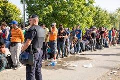 Övervaka att bevaka den väntande linjen av flyktingar i Tovarnik Royaltyfria Bilder