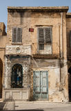 Vervallen oud huis met een klein heiligdom in de voorzijde Stock Afbeelding