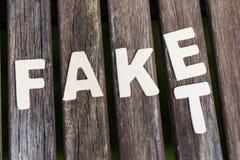 Vervalsing, feit, als tekst, brieven op hout stock afbeelding