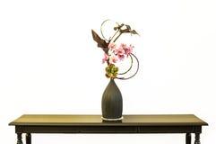 Vervalste bloem in een kruik op een lijst Stock Afbeeldingen