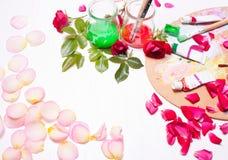 Verven en borstels met roze bloemblaadjes Werkplaats van kunstenaar, ontwerper Stock Foto
