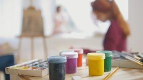 Verven en kunstlevering voor kunstenaars die artistiek etude witn naakt model uitvoeren stock footage