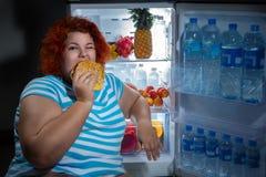 Överviktig kvinna med kylskåpet Royaltyfri Foto