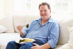 Överviktig man som äter sunt målsammanträde på soffan Royaltyfria Bilder