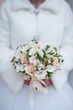 Övervintra bröllopbuketten i händer av bruden Arkivfoto