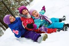 Övervintra gyckel, snö, barn som sledding på vintertid Arkivfoto