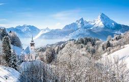 Övervintra landskapet i de bayerska fjällängarna med kyrkan, Bayern, Tyskland Fotografering för Bildbyråer